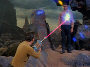 Kirk fires a phaser rifle at Mitchell